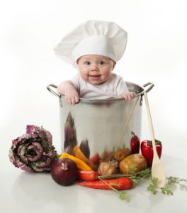 Portrait of a smiling baby sitting inside a large cooking stock pot surrounded by vegetables and food, isolated on white